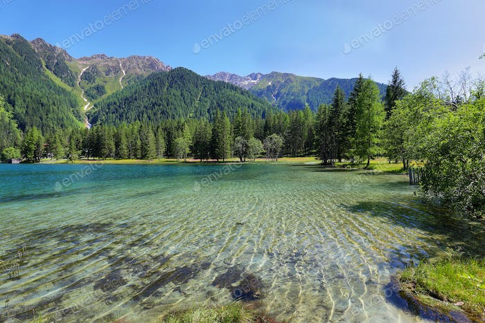 Anterselva Lake surrounded by red and yellow flowers, Trentino Alto Adige, Italy