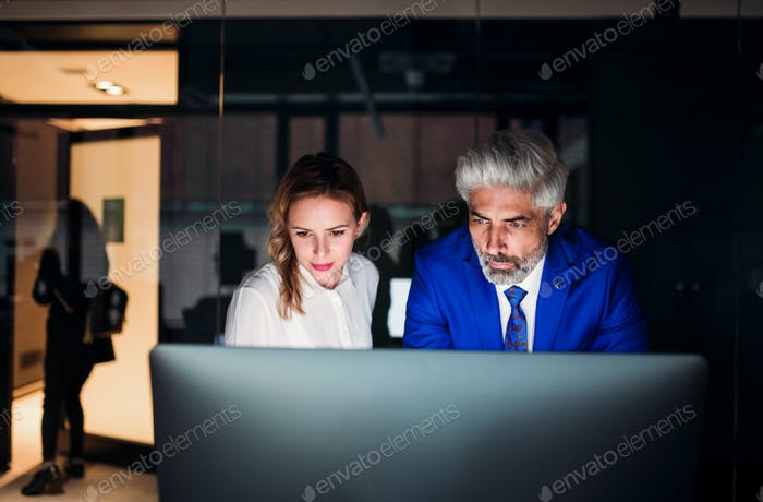 Two business people in an office at night., working