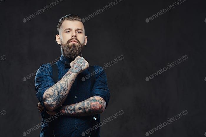 Портрет красивого старомодного хипстера в синей рубашке и подтяжках в темной студии.