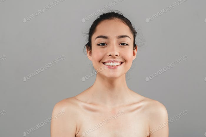 Woman beauty face portrait isolated on gray with healthy skin and white teeth smile