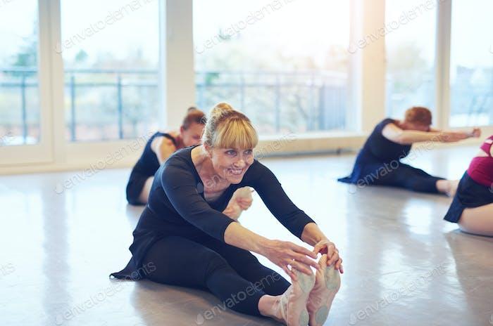 Smiling adult women doing ballet sitting on floor