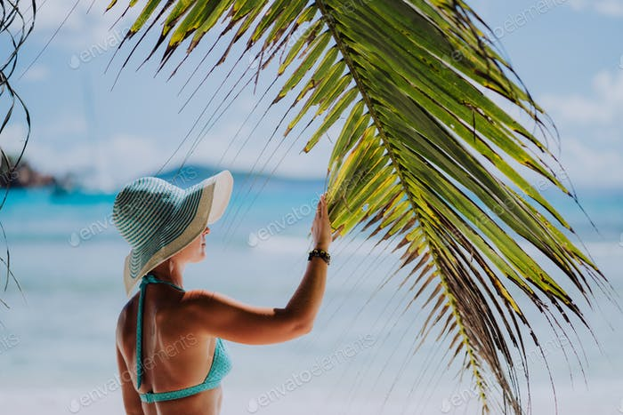 Woman on the beach touching palm tree leaf shadow wearing blue hat. Luxury paradise recreation
