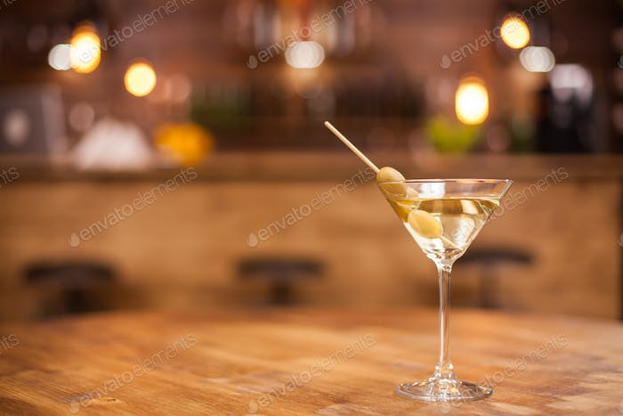Single glass of dry martini in a restaurat over a wooden table