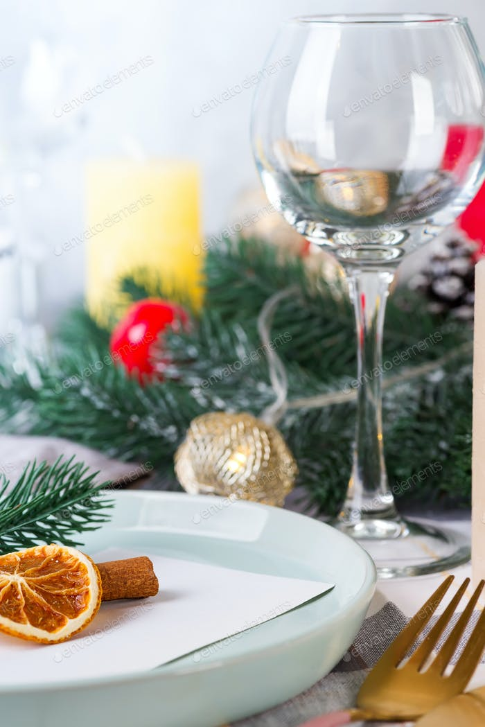 Festive Christmas and New Year details table setting with dry orange and wine glass on a gray