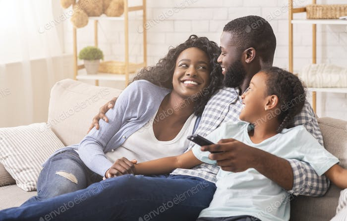 Cheerful Black Family Having Fun Together Watching TV Show