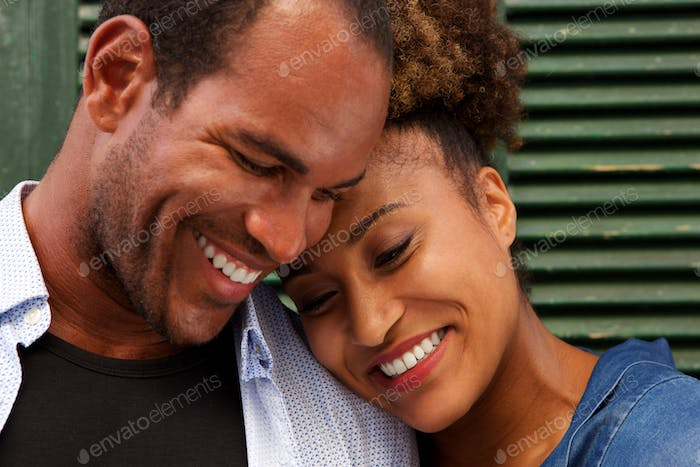 Close up cheerful couple in love smiling on green background