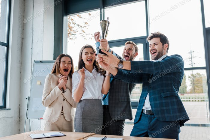 happy businessmen and multicultural businesswomen holding trophy in office
