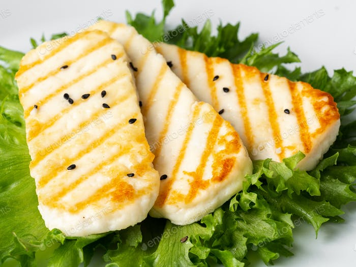 Grilled Halloumi, macro fried cheese with  lettuce salad.  Balanced diet, white plate, side view
