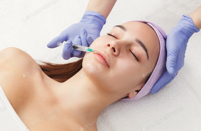 Woman getting beauty injection at salon
