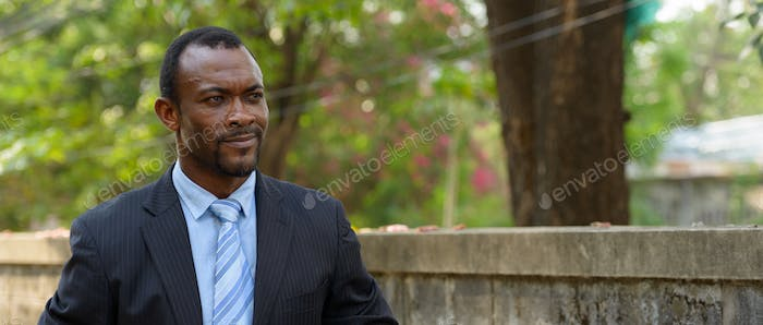 Portrait of handsome African bearded businessman outdoors