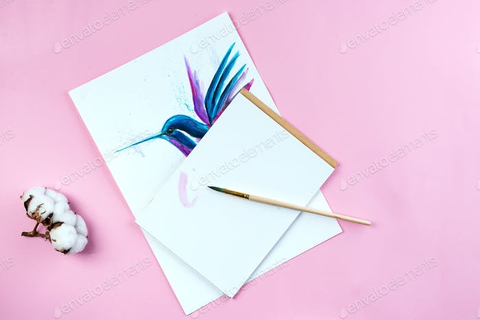 Top view of desktop workplace artist with tools - brushes, watercolor paint, notebook on pink
