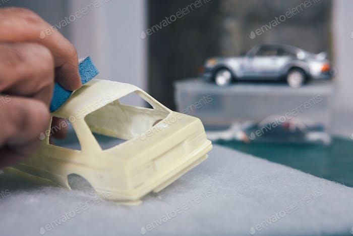 Person polishing miniature auto