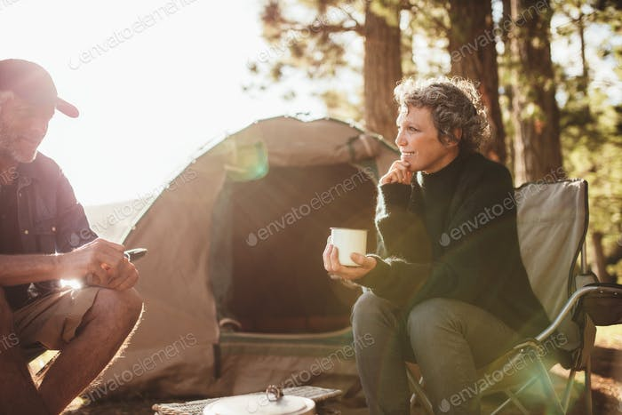 Relaxed couple sitting outside tent while camping nearby lakesid