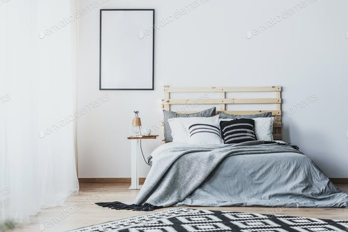 Mockup of empty poster in white bedroom interior with grey woode