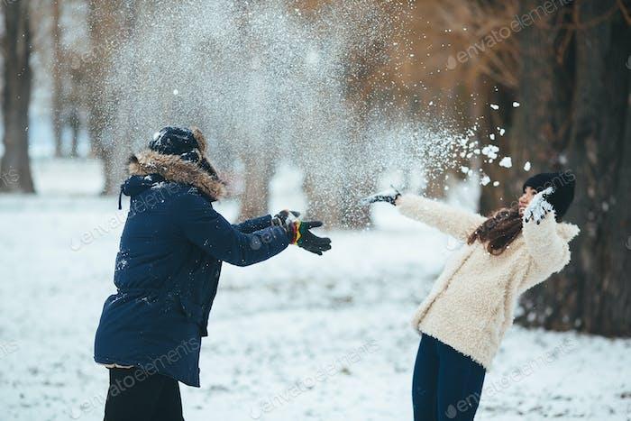 Junge und Mädchen spielen mit Schnee