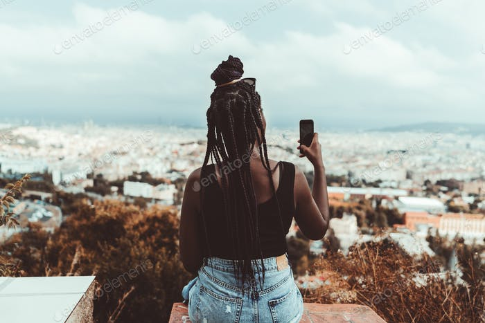 Black girl photographing a cityscape