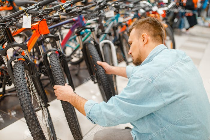 Man checks bicycle tyre, shopping in sports shop