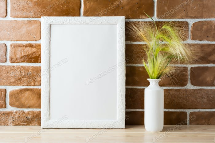 White frame mockup with ornamental grass near exposed brick wall