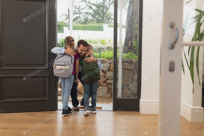 Front view of Caucasian father embracing his children at door in a comfortable home