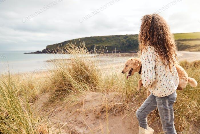Girl Carrying Pet Dog Exploring Sand Dunes On Winter Beach Vacation