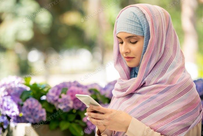 Young Arabian woman wearing hijab scrolling in her smartphone