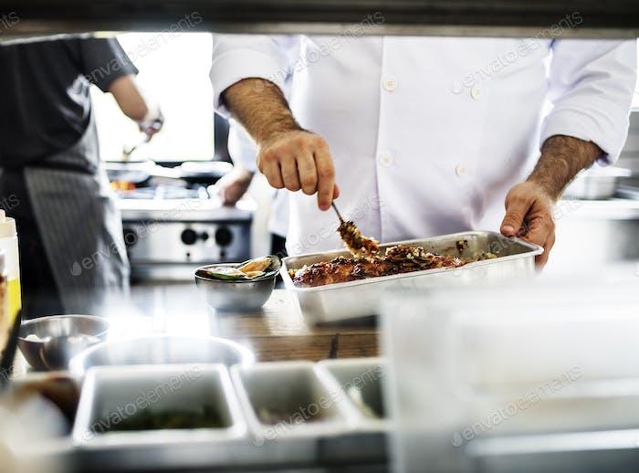 Chefkoch, die ein Fleisch mariniert