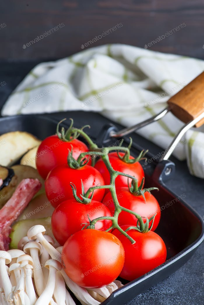 Fresh cherry tomatoes grill pan as cooking ingredients for dish on a dark background with napkin
