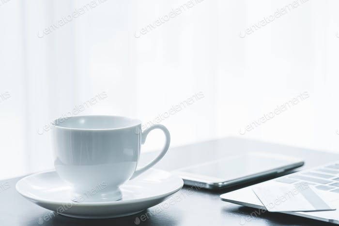 cup of coffee and credit cards on laptop