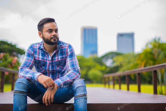 joven guapo indio hombre en parque pensamiento