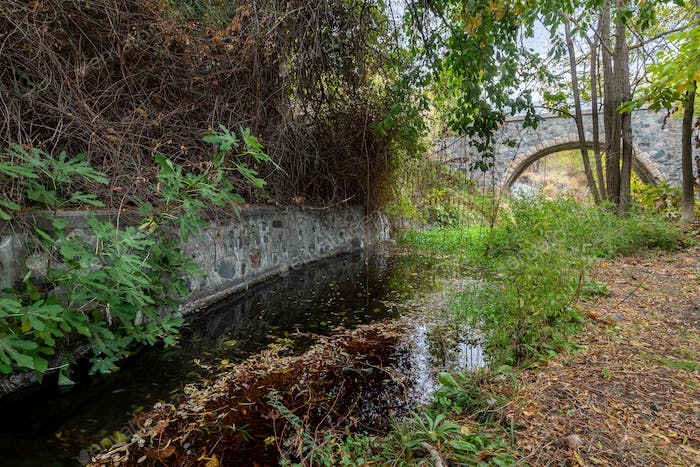 Medieval stoned bridge water flowing in the river in autumn