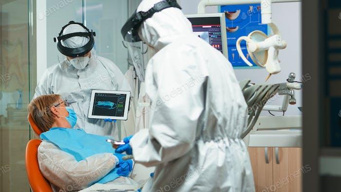 Orthodontist in coverall using tablet explaining dental x ray