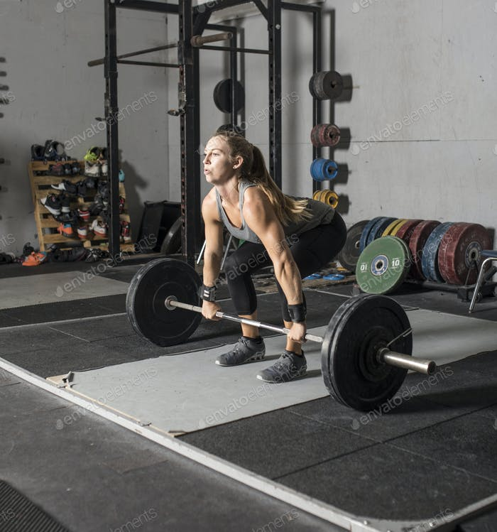 Female weight lifter preparing to lift heavy barbell.