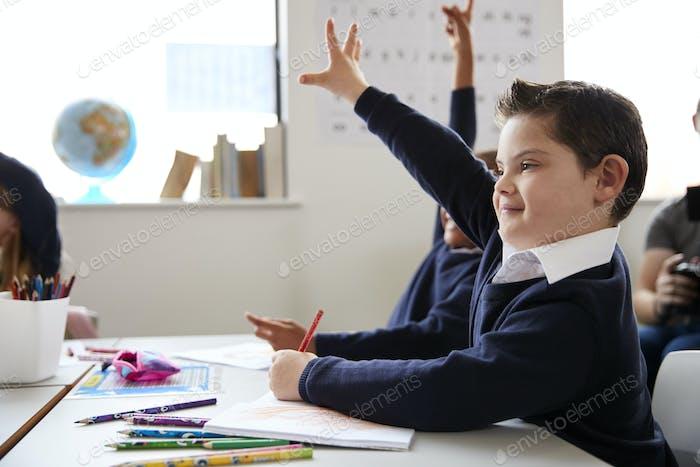 Schuljunge mit Down-Syndrom sitzt an einem Schreibtisch hob seine Hand in einer Grundschule Klasse