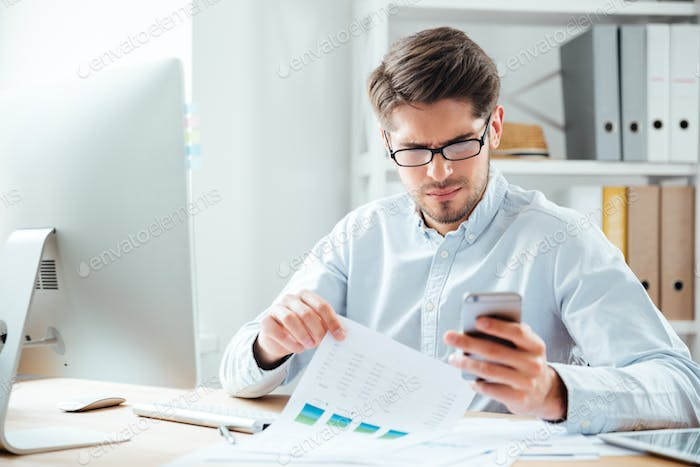 Portrait of a businessman using mobile phone in the office