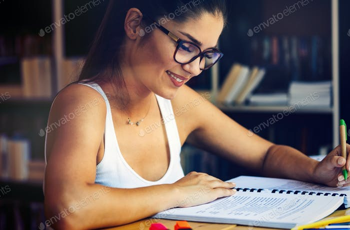 Beautiful student girl studying, reading book at home