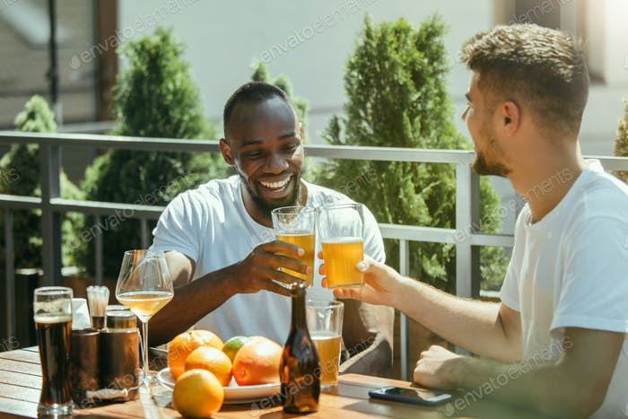 Young men drinking beer and celebrating together