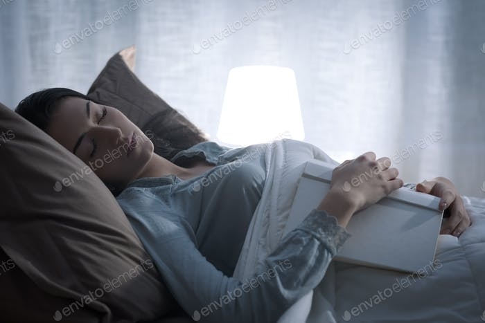 Woman falling asleep while reading a book