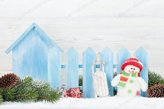 Christmas gift boxes, snowman toy and fir tree branch