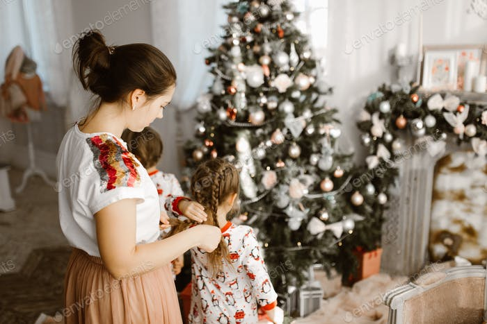 ?aring mother braids her little daughter's braid while second daughter decorates a New Year&#39