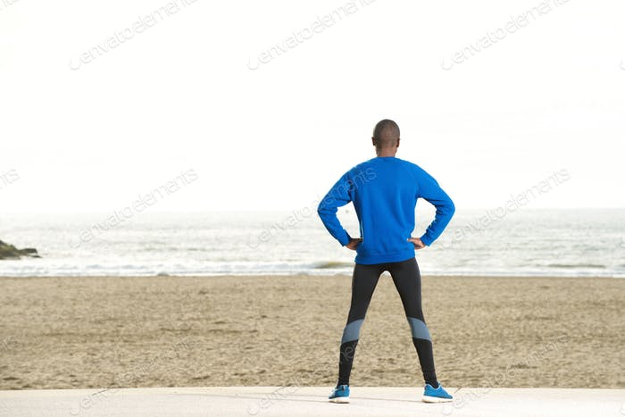 back of sport man looking at sea