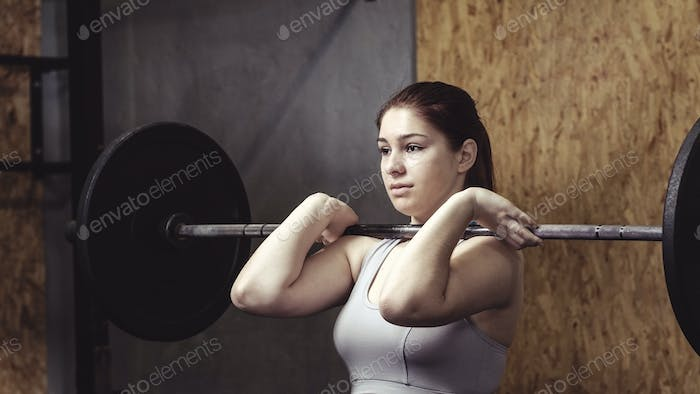 Strong muscular woman working out with a barbell