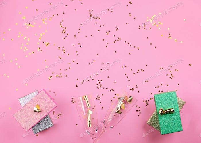 Champagnerflöten und Geschenke auf rosa. Konfetti