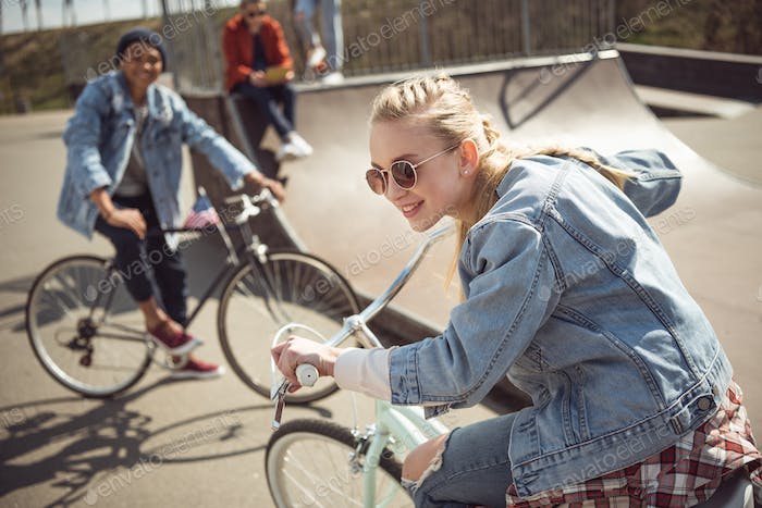 Teenagers Having Fun and Riding Bicycles in Skateboard Park, Bike Riding City Concept