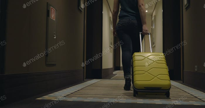 Woman with trolley bag looking for room in hotel