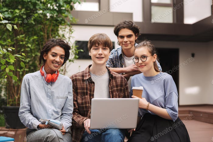 Group of young cheerful students sitting on bench and working on laptop together