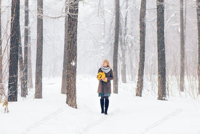 Schönes junges Mädchen in einem weißen Winterwald