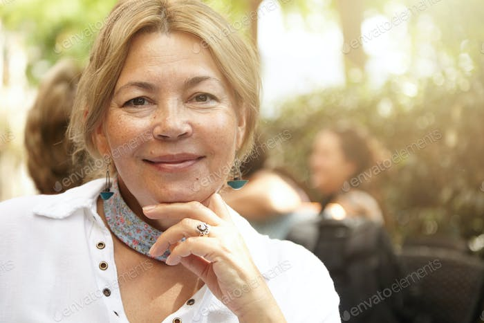 Portrait of beautiful Caucasian elderly female wearing stylish scarf looking at camera and smiling w