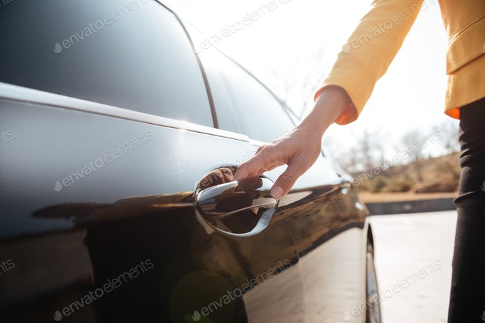 Businesswomen opening the door of black car