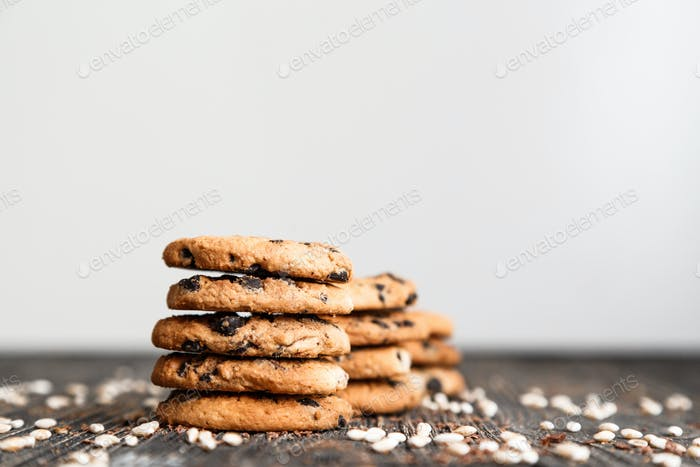 Stacks of chocolate chip cookies on dark table with copy space on top