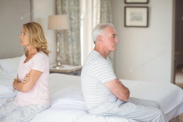Upset senior couple sitting back to back on bed